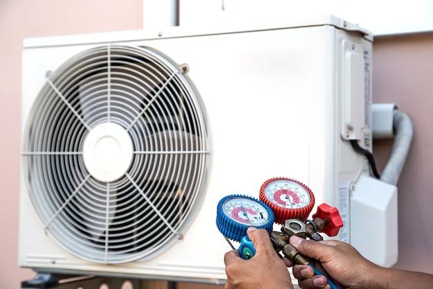 O técnico está usando manômetro múltiplo para verificar e encher os condicionadores de ar de fábrica