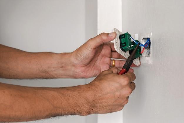 O técnico está usando um alicate para instalar o plugue de energia na parede