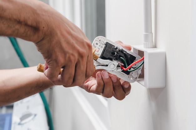 O técnico está usando uma chave de alicate para instalar o plugue de energia na parede.