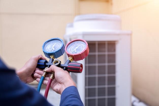 O técnico está verificando o ar condicionado, medindo o equipamento para encher os aparelhos.