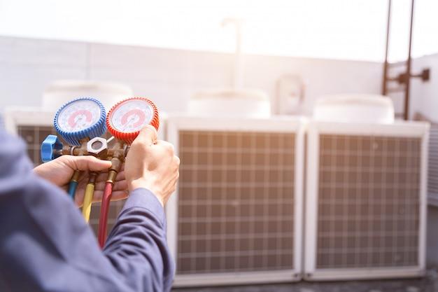 O técnico está verificando o condicionador de ar, equipamento de medição para encher condicionadores de ar.