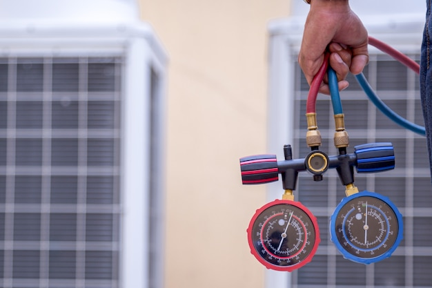 O técnico está verificando o condicionador de ar, medindo o equipamento de enchimento dos condicionadores de ar.
