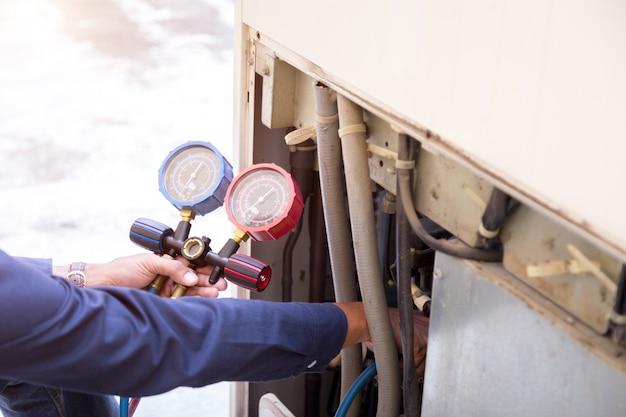 O técnico está verificando o equipamento de medição do condicionador de ar quanto ao enchimento dos condicionadores de ar.