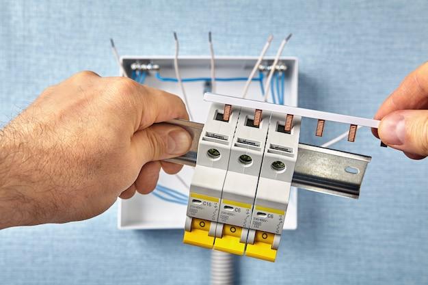 O técnico monta um quadro elétrico ou quadro de distribuição.