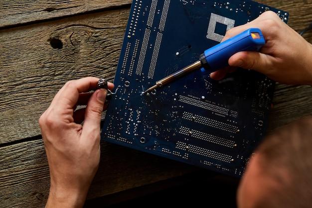 O técnico ou engenheiro está focado na reparação da placa de circuito com ferro de soldar.