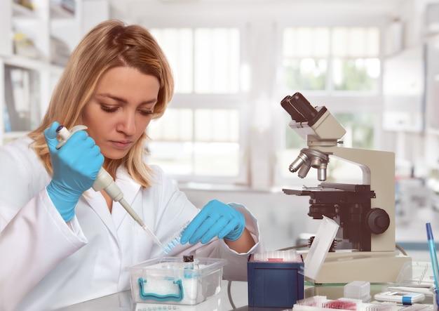 O técnico ou o cientista fêmea novo carregam a amostra líquida em tubos de ensaio
