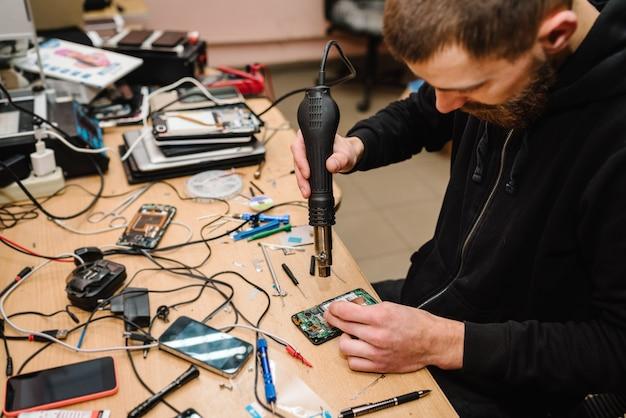 O técnico que repara a placa-mãe do smartphone no laboratório. conceito de hardware de computador, telefone celular, eletrônico, reparação, atualização, tecnologia. homem mostrando o processo de reparo do telefone na oficina.