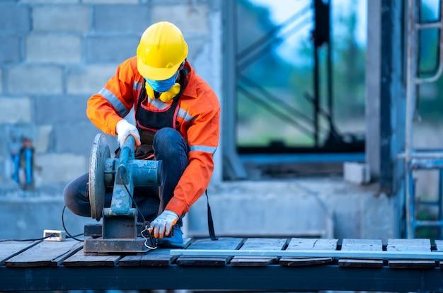 O técnico que trabalha com o moedor de aço está cortando o tubo de ferro da construção no canteiro de obras.
