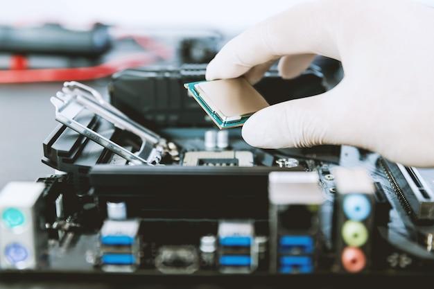 O técnico substitui o microchip da cpu no soquete da cpu na placa-mãe