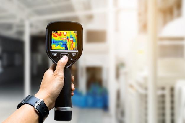 O técnico usa a câmera de imagem térmica para verificar a temperatura na fábrica
