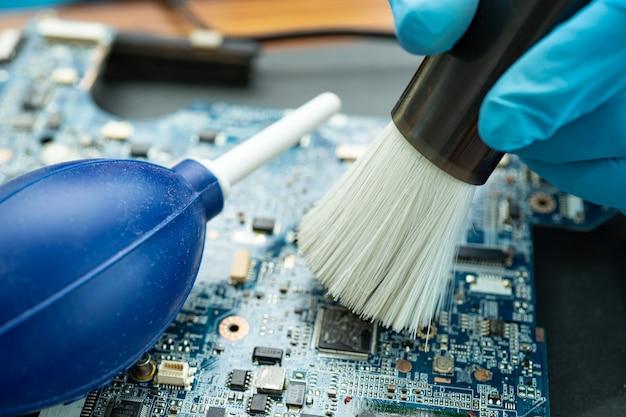 O técnico usa escova e bola de ar para limpar a poeira no computador da placa de circuito