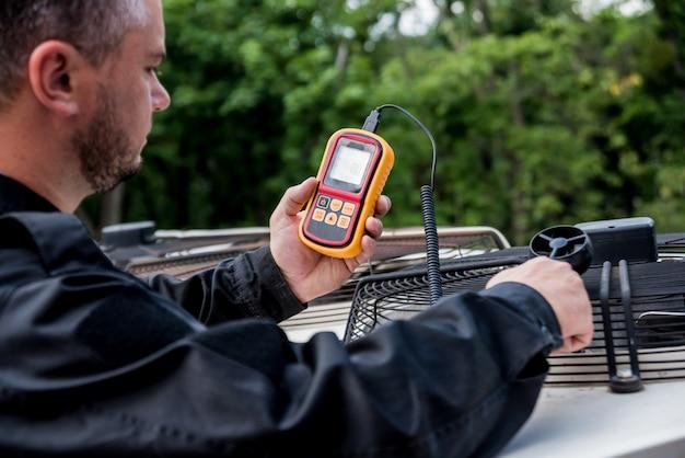 O técnico usa um anemômetro portátil que mede a medição de fluxo de ar, velocidade e pressão do vento.