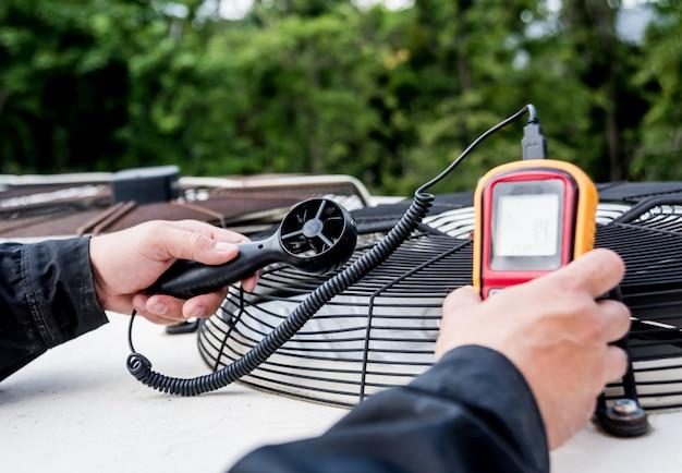 O técnico usa um anemômetro portátil que mede a medição do fluxo de ar, a velocidade e a pressão do vento.