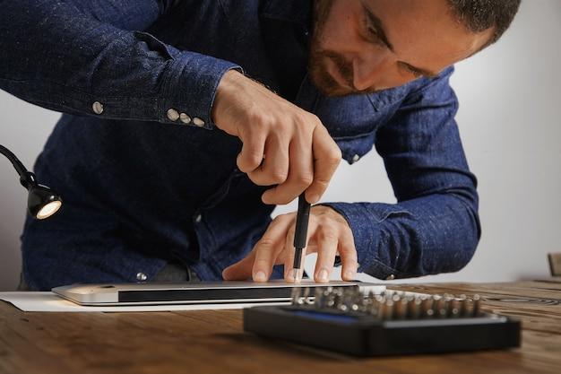 O técnico usa uma chave de fenda para fechar a parte superior traseira do laptop do computador pessoal após o serviço de reparo e limpeza em seu laboratório