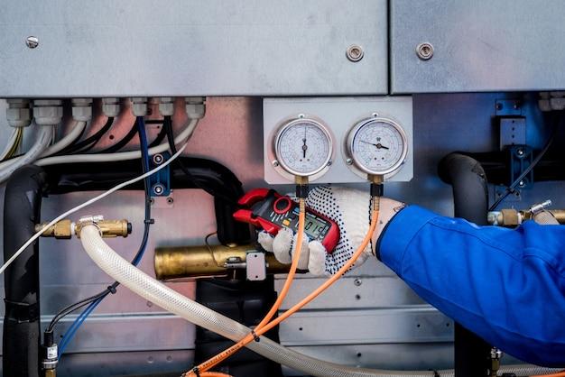 O técnico verifica as linhas de energia do trocador de calor com pinças de corrente