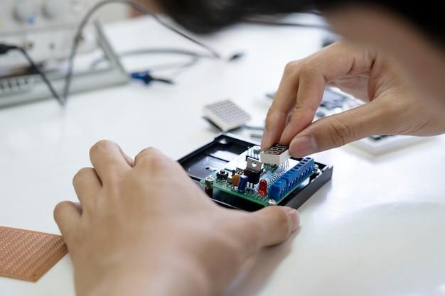 O técnico verifica o dispositivo eletrônico.