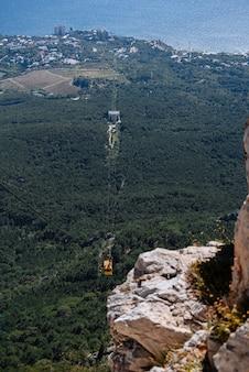 O teleférico no funicular de verão desce da vista da montanha das montanhas para o mar