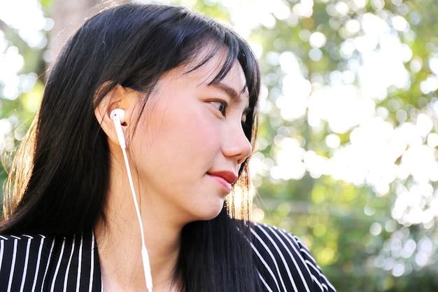 O telefone asiático do uso da mão da mulher de negócio da pele bronzeado bonita encantador e escuta música da música do auscultadores na sala. apresentando seu produto