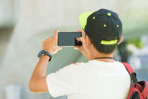 O telefone celular esperto do uso do homem toma a opinião do picofarad da foto, conceito da tecnologia.