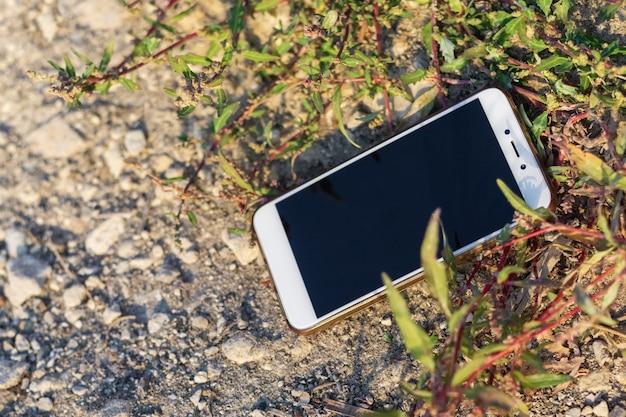 O telefone celular está caído no chão entre as plantas, o tema da ecologia, as tecnologias de proteção da natureza, o conceito de proteção do ecossistema