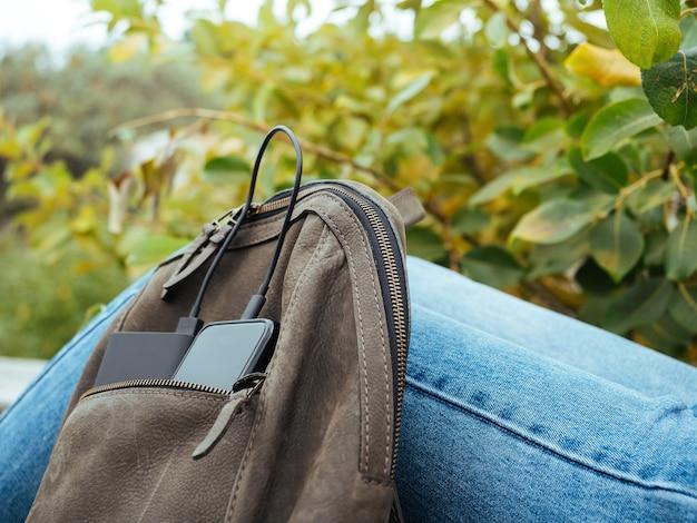 O telefone é carregado usando um banco de energia. uso de tecnologias modernas na vida cotidiana