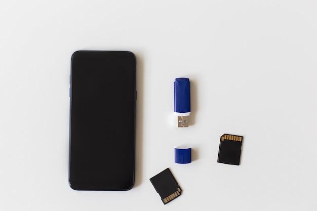 O telefone e o pen drive em uma superfície branca