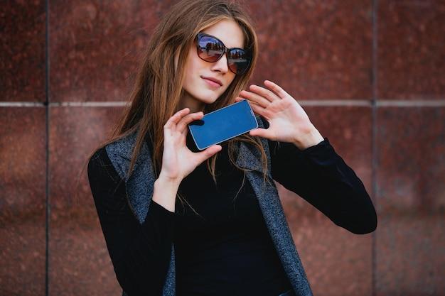O telefone segura uma garota contra a parede