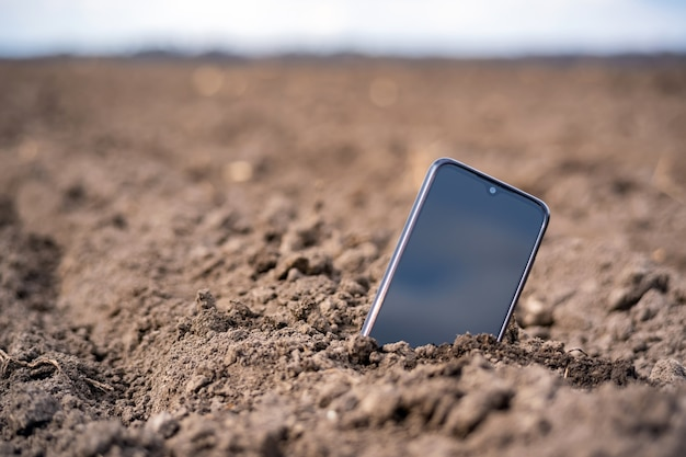 O telefone sobressai do solo no campo.