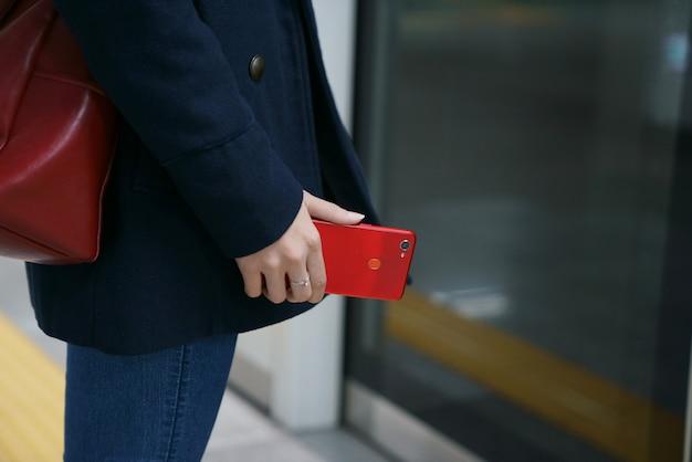 O telefone vermelho é segurado na mão dela
