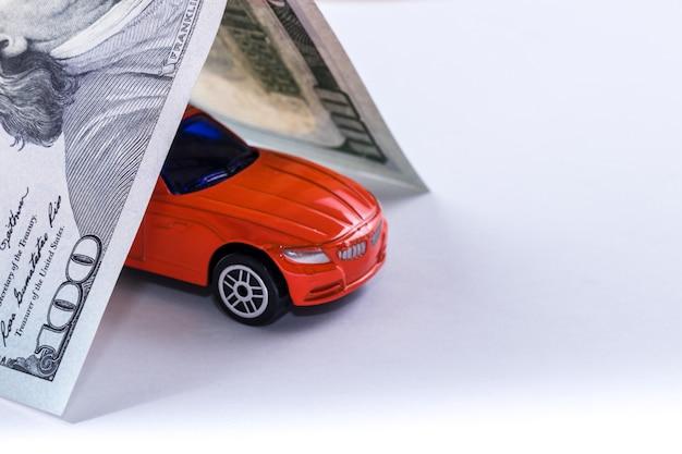 O telhado da nota de dólar do close-up cem cobre o brinquedo vermelho do carro isolado no branco.