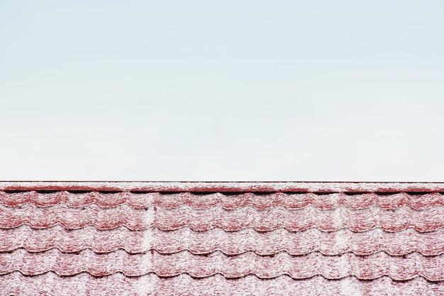 O telhado está coberto de neve. fundo. telhado vermelho. telhado contra o céu