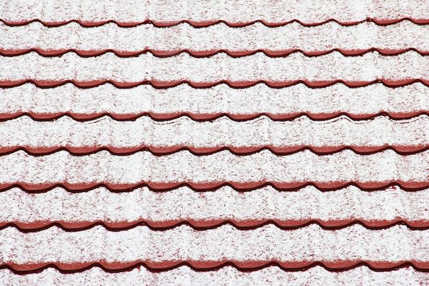 O telhado está coberto de neve. fundo. telhado vermelho