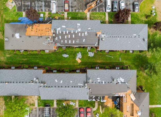 O telhado repara a substituição velha do telhado com as telhas novas de um apartamento