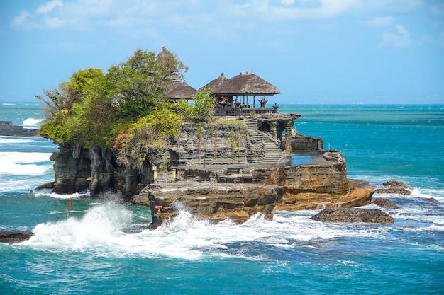 O templo de tanah lot com ondas fortes. indonésia