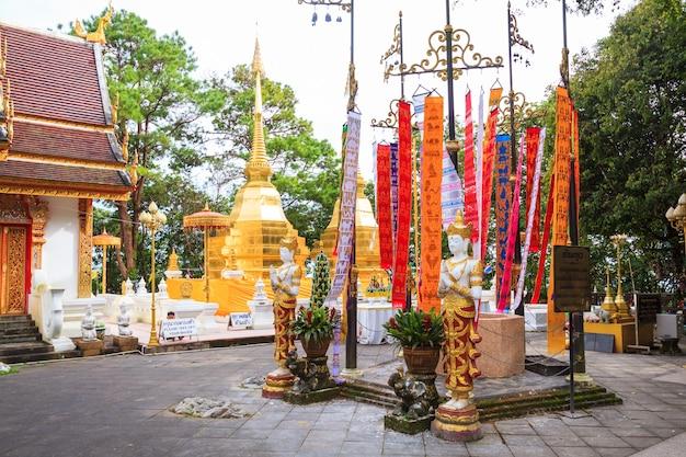 O templo wat phra that doi tung, de domínio público, tem dois pagodes dourados contendo buda.