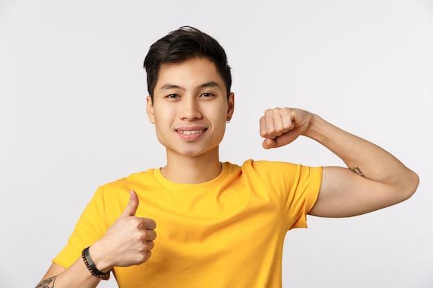 O tempo aumenta. atraente jovem asiático de camiseta amarela, mostrando o músculo e o polegar para cima, sorrindo, incentive a fazer exercícios físicos, venha a academia juntos, quer ganhar bíceps forte