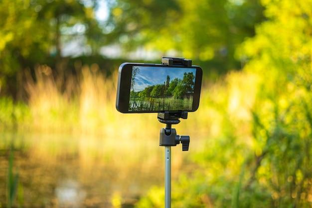 O tempo de gravação de fotos e vídeos em celulares no stick de selfie, tripé, fundo da natureza, conceito de fotografia móvel para viagens