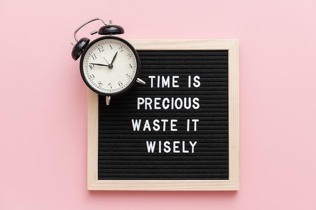 O tempo é precioso desperdiçar sabiamente, citação motivacional em papelão e despertador preto na rosa