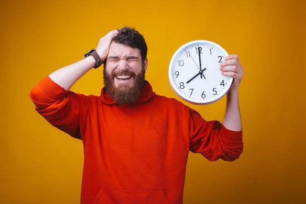 O tempo é tão rápido. foto de cara barbudo, com os olhos fechados e a mão na cabeça está segurando um relógio branco.