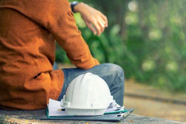 O tempo usando capacete de segurança de equipamentos de proteção no canteiro de obras com engenheiro