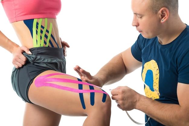 O terapeuta cola fitas kinesio na perna da mulher