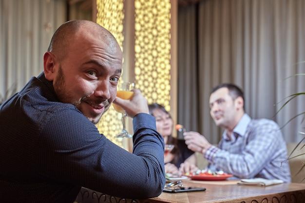 O terceiro é supérfluo. casal apaixonado está jantando em um restaurante com um amigo solitário