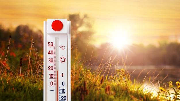 O termômetro mostra 20 graus de calor na natureza perto do rio durante o pôr do sol