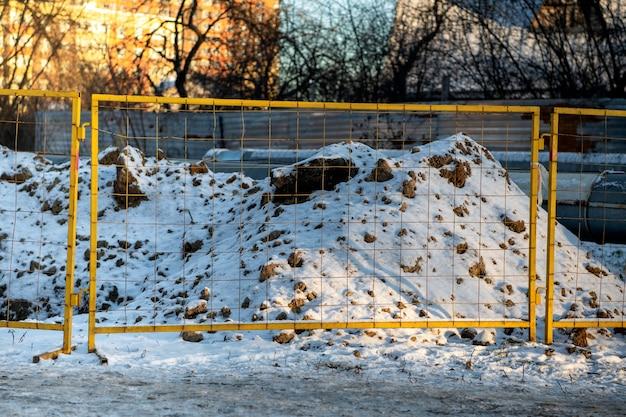 O terreno escavado na neve no inverno é cercado com uma cerca de metal com malha e fita isolante