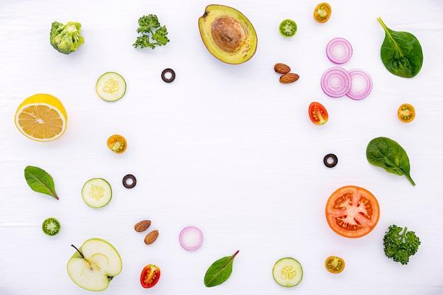 O teste padrão do alimento com os ingredientes crus do plano da salada coloca em de madeira branco.