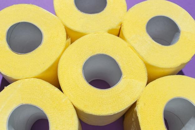 O teste padrão do papel higiênico amarelo brilhante rola no fundo roxo.