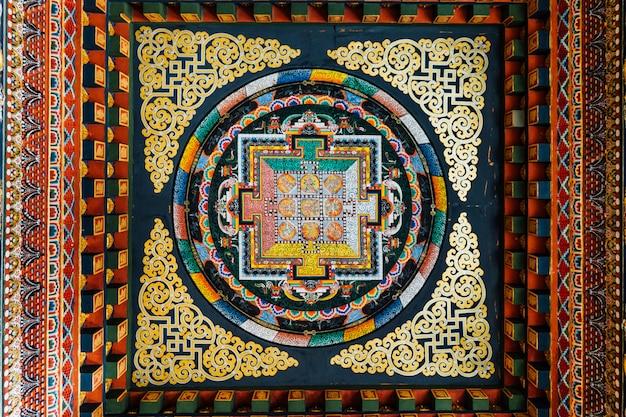 O teto decorado que diz sobre a história do senhor buddha na arte butanesa dentro do monastério butanês real em bodh gaya, bihar, india.