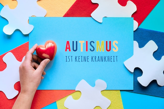 O texto alemão significa que o autismo não é uma doença. design criativo para o dia mundial da conscientização do autismo. mão segure o coração de pedra.