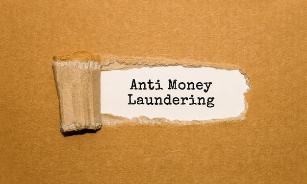 O texto anti-lavagem de dinheiro aparecendo atrás de papel pardo rasgado