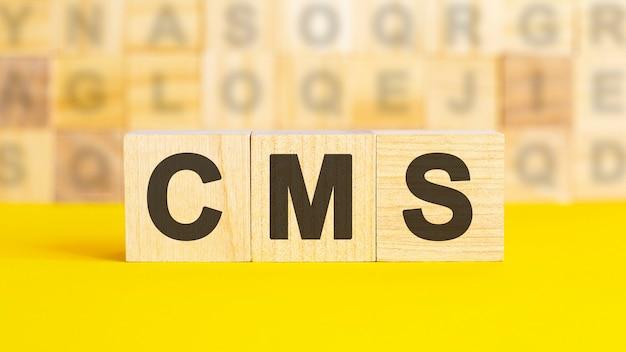 O texto cms é escrito em cubos de madeira sobre uma superfície amarela brilhante. no fundo, há fileiras de cubos com letras diferentes. conceito de negócios. cms - abreviação de content management system
